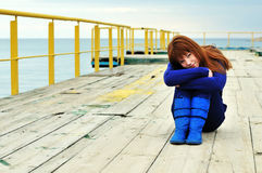 Redheaded girl on a pier. Young redheaded girl on a pier near the sea royalty free stock image