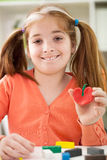 Redheaded girl with pigtails and freckles made of plastici Stock Images
