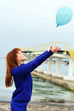 Redheaded girl pushing balloon out Stock Photo