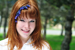 Redheaded girl in the spring forest. With flowers in her hair Stock Images