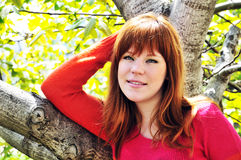 Redheaded girl under the tree. Redheaded girl is standing under the tree and smiling Stock Photo