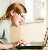 Redheaded girl uses  home computer Stock Images