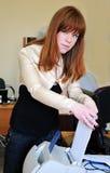 Redheaded girl using printer. Redheaded beautiful young girl is using printer stock photos