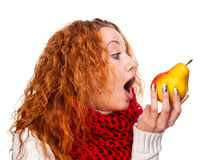 Redheaded girl wants to eat a pear Royalty Free Stock Photos