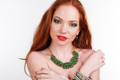 Redheaded girl is wearing green necklace. Portrait of beautiful redheaded girl with fashion colorful makeup is wearing green necklace stock photography
