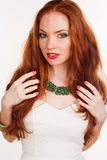 Redheaded girl is wearing green necklace. Portrait of beautiful redheaded girl with fashion colorful makeup is wearing green jewelry Stock Photo