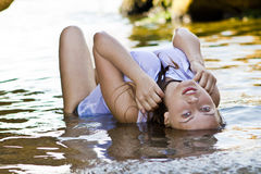 Redheaded girl in a wet white T-shirt Royalty Free Stock Images