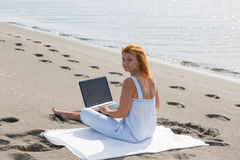 Redheaded girl working at a laptop sitting on the Stock Photography