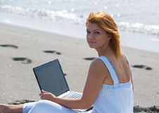 Redheaded girl working at a laptop sitting on the Royalty Free Stock Image