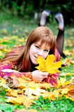 Redheaded gril in autumn forest. Redheaded gril lating on the meadow in autumn forest Stock Images