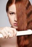 Redheaded kvinna med hår som rätar ut järn Royaltyfri Fotografi