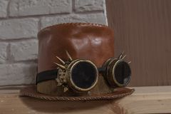 Redheaded leather hat-cylinder and steampunk goggle glasses. Redheaded leather hat-cylinder and steampunk goggle pilot`s glasses royalty free stock photography