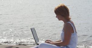 Redheaded Mädchen, das an einem Laptop sitzt auf dem Strand arbeitet stock video