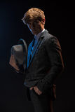 Redheaded man in a plaid suit with hat. In hand on a black background in the studio royalty free stock photos