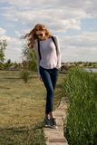 Redheaded model is teetering on the parapet Royalty Free Stock Image