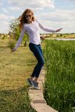 Redheaded model is teetering on the parapet Royalty Free Stock Photo
