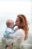 Redheaded mother is tenderly kissing her sleepy baby boy Stock Images