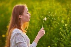 Redheaded nastoletni dziewczyny dmuchanie na dandelions zdjęcie royalty free