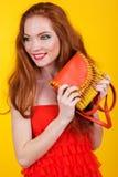 Redheaded pretty girl with fashion handbag. Portrait of beautiful redheaded girl with fashion colorful makeup is holding orange fashion handbag Stock Photos