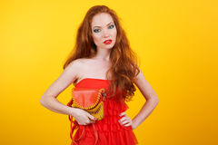 Redheaded pretty girl with orange handbag Stock Photos