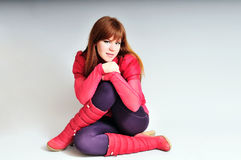 Redheaded sitiing girl. Wearing red clothing Stock Photos