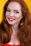 Redheaded smiling girl with fashion makeup. Portrait of beautiful redheaded girl with fashion colorful makeup and long hair Stock Photo