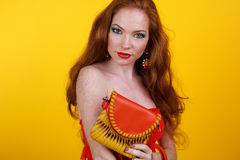 Redheaded smiling girl with fashion purse. Portrait of beautiful redheaded girl with fashion colorful makeup is holding orange purse Royalty Free Stock Images