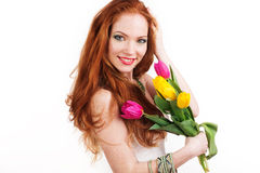 Redheaded smiling girl is holding tulips Royalty Free Stock Photography