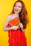 Redheaded smiling girl with orange handbag Stock Photos