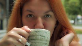 Redheaded tausendjährige Frauen genießen Getränk am Freilicht lizenzfreie stockfotos