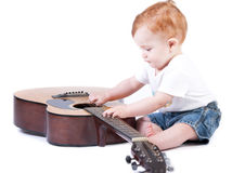 Toddler playing with old guitar Stock Images