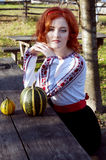 Redheaded Ukraininan girl sitting at the table. Redheaded ukrainian girl sitting at the table in the village Stock Photography