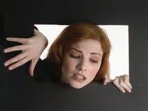 Redheaded vrouw die uit een zwarte doos beklimt stock foto's