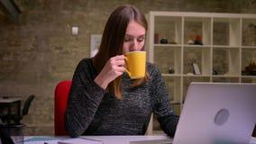 Redheaded vrouw drinkt koffie en werkt zorgvuldig met laptop in het bureau stock footage
