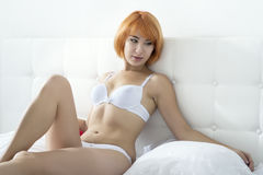 Redheaded woman in the bedroom Stock Photography
