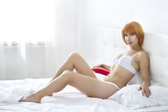Redheaded woman in the bedroom Royalty Free Stock Images