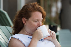 Redheaded woman drinking cup of coffee. Redheaded woman drinking a cup of coffee from white mug while sitting on deck chair outdoors in coastal North Carolina Stock Photos