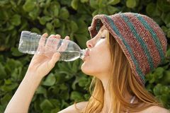 Redheaded woman drinking water. Stock Image