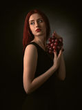 Redheaded woman with grape. Beautiful redheaded woman in a black dress with grape Stock Image