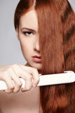 Redheaded woman with hair straightening irons Royalty Free Stock Photography