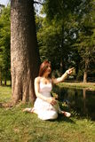 Redheaded Woman Pointing. Redheaded young woman sitting in an outdoor wooded setting, pointing at something out of camera range Royalty Free Stock Image