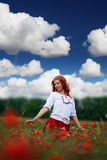 Redheaded woman in poppy field. Beauty redheaded woman in poppy field Royalty Free Stock Photography