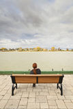 Woman looking at river. A redheaded woman seated and relaxing on a wood and metal bench on a quay and looking at the river in front of her under cloudy skies Royalty Free Stock Photography
