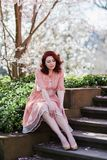 Redheaded woman sitting on the stairs. Portrait of a redheaded woman who sits on the stairs in a park Stock Image