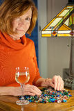Redheaded woman sorting beads. Attractive middleaged redheaded woman with a glass of wine sorting beads under a tiffany lamp Stock Photos