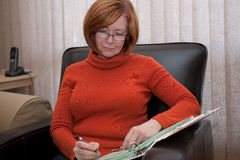 Redheaded woman teacher marking homework in a 3-ri. Attractive, middleaged, redheaded woman teacher marking homework in a 3-ring binder, while seated in a Royalty Free Stock Image