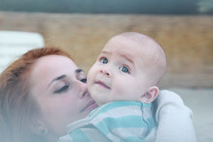 Redheaded woman is tenderly kissing baby boy. Image with selective focus Royalty Free Stock Image