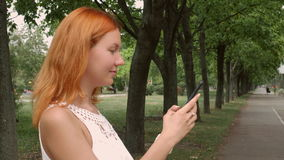 Redheaded woman texting on mobile phone. Young ginger student standing on the street in park or city using smart phone messaging. Beautiful millennial girl stock footage