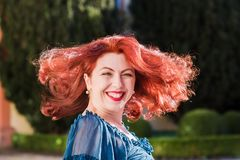 Redheaded woman turns her head. Smiling redheaded beautiful woman turns her head Royalty Free Stock Images