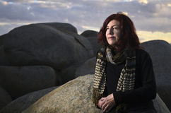 Redheaded  woman wearing scarf in coastal scene Stock Images